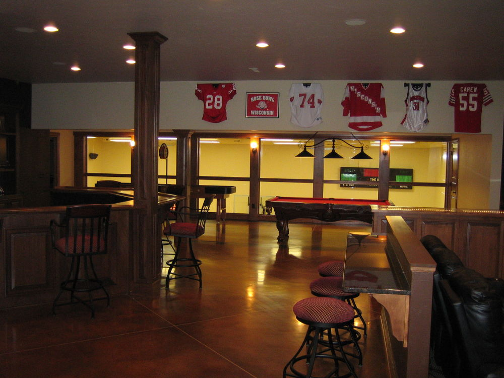 Basement sports bar lounge with brown concrete floor
